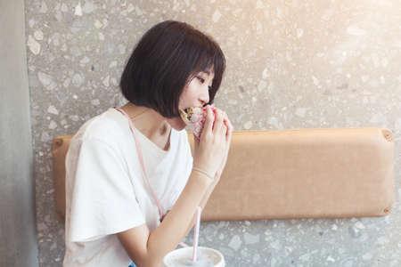 Girl having fun eating burger in restaurant Imagens