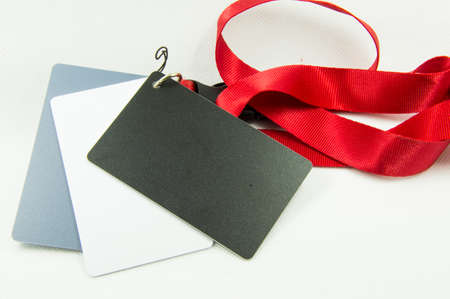 accolade: white, grey and black card on a red ribbon on a white background