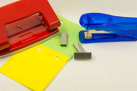 hole punch: sheets of paper and a hole punch on a white background