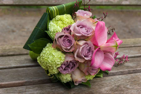 trillium: Wedding bouquet with roses on a wooden bench