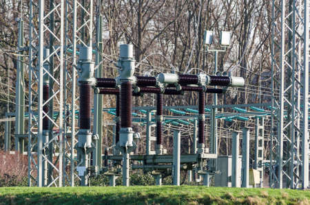 isolator insulator: power plant with isolation objects in front of trees Stock Photo