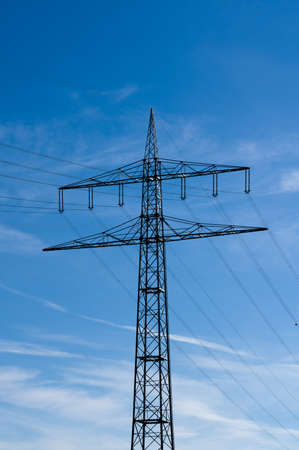 energy needs: high-voltage electricity pylons against blue sky with clouds