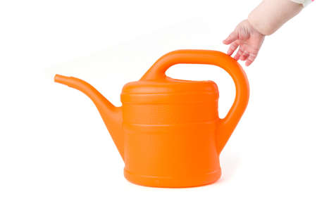 Baby trying to grab a orange watering can on white background