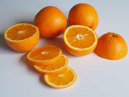 Orangen auf hellem Hintergrund ganz und gehackt