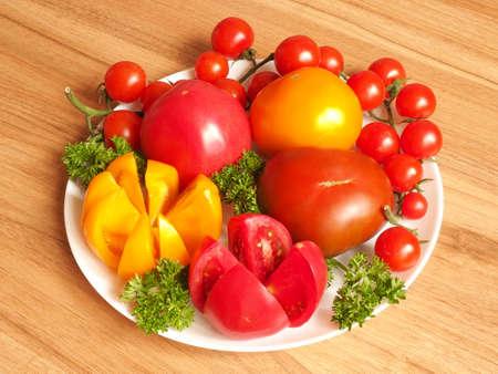 pomodori con verdure su un piatto su un tavolo di legno Archivio Fotografico