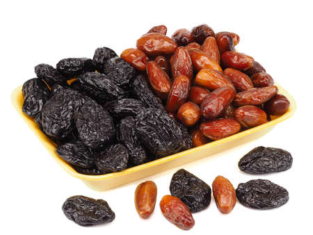 Mixed dried fruit: prunes and dates on a white background