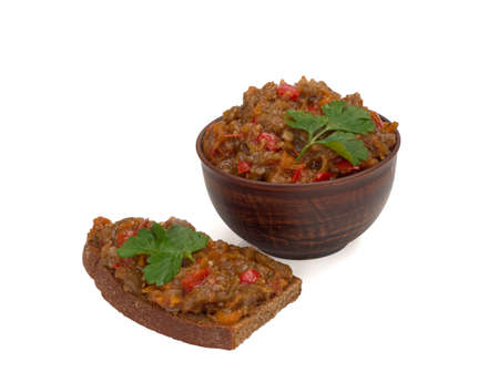 eggplant caviar in the bow and on the piece of bread. White background