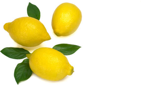 Three whole yellow lemons with green leaves isolated on a white background