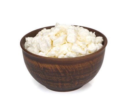 Fresh homemade cottage cheese in a bowl on white background Imagens