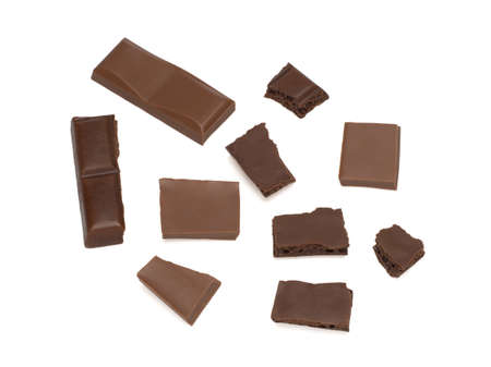 close up of dark porous chocolate and milk chocolate pieces on a white background