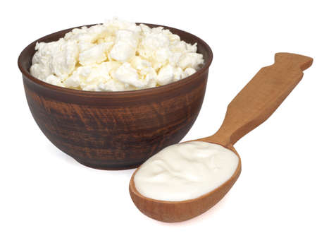 Fresh homemade cottage cheese in a bowl and a spoon with sour cream on white background Imagens