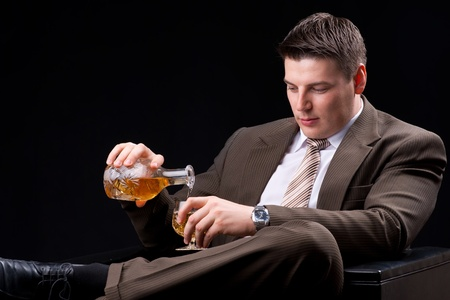 Young businessman sitting on a couch with an alcoholic beverage  photo
