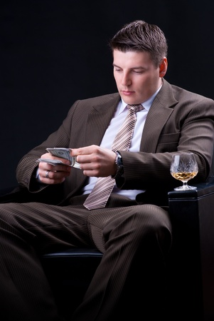 Businessman with drinks, cigars and money count  photo