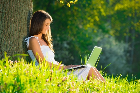 Beautiful young woman relaxing on grass with laptop photo