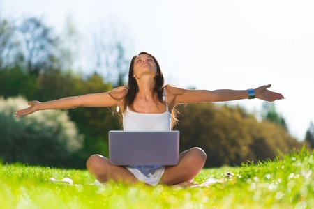 field study: Portrait of an excited young female enjoying success while using a laptop on grass Stock Photo