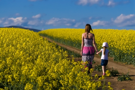 Beautiful young mother and daughter walking in the Field of rape  photo