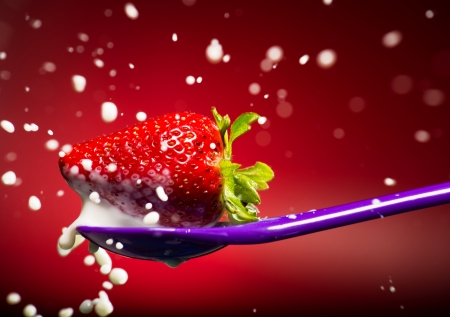 Strawberry on the purple spoon and milk splash photo