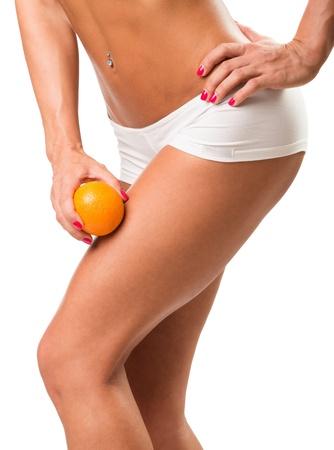 cuerpo femenino perfecto: Una chica joven en ropa interior con una naranja sobre un fondo blanco