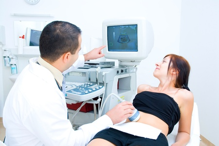 A doctor shows the patient on the monitor of the ultrasound image  Imagens
