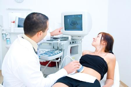 Un médecin indique au patient sur l'écran de l'image ultrasonore