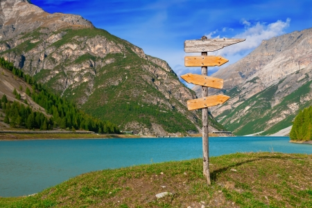 Empty Direction signpost a beautiful lake and mountains in the background
