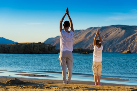 Mother and daughter doing yoga exercise on the beach Stock Photo - 22101724