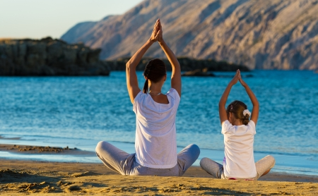 Mother and daughter doing yoga exercise on the beach Stock Photo - 22101725