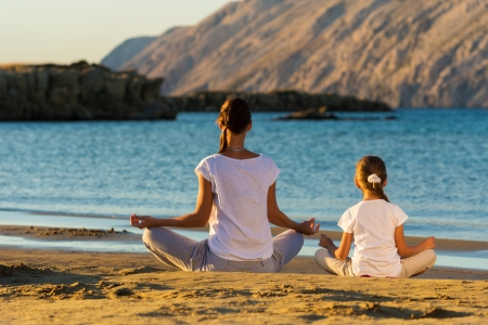Mother and daughter doing yoga exercise on the beach Stock Photo - 22101727