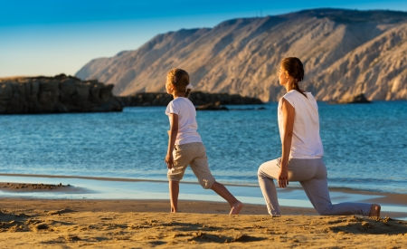 Mother and daughter doing yoga exercise on the beach Stock Photo - 22101728