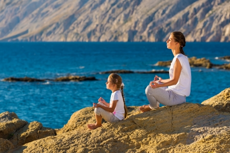 Mother and daughter doing yoga exercise on the beach Stock Photo - 22101736
