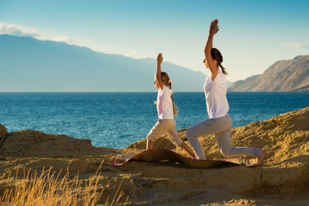 Mother and daughter doing yoga exercise on the beach Stock Photo - 22101851