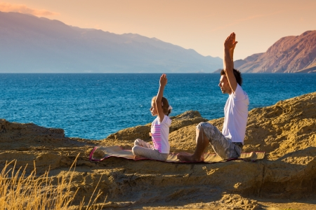 Mother and daughter doing yoga exercise on the beach Stock Photo - 22101871