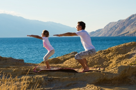 Mother and daughter doing yoga exercise on the beach Stock Photo - 22101872