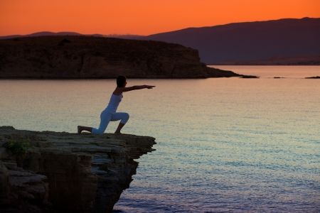 Silhouette of a woman doing yoga on the beach at sunset Stock Photo - 22101888