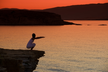 Silhouette of a woman doing yoga on the beach at sunset Stock Photo - 22101889