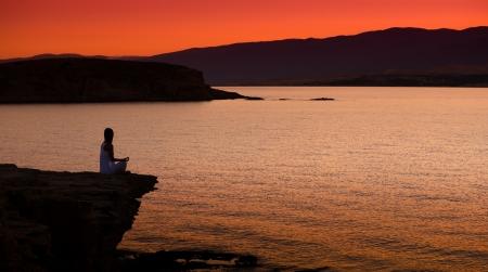 Silhouet van een vrouw doet yoga op het strand bij zonsondergang