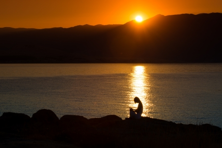 Silhouette of a woman doing yoga on the beach at sunset Stock Photo - 22101911