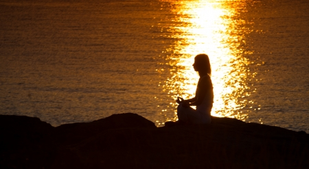 Silhouette of a woman doing yoga on the beach at sunset Stock Photo - 22101958