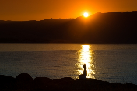 Silhouette of a woman doing yoga on the beach at sunset Stock Photo - 22101960