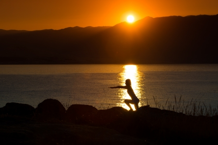 Silhouette of a woman doing yoga on the beach at sunset Stock Photo - 22101962