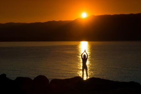 Silhouette of a woman doing yoga on the beach at sunset Stockfoto