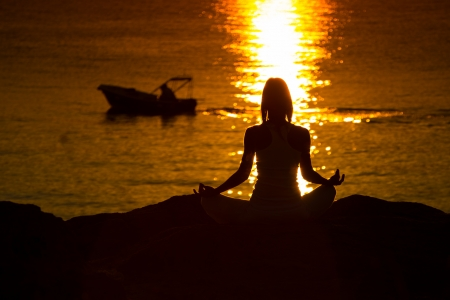 Silhouette of a woman doing yoga on the beach at sunset Stock Photo - 22101968