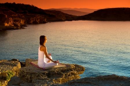 energia espiritual: Atractiva joven en una posici�n de yoga en una playa hermosa