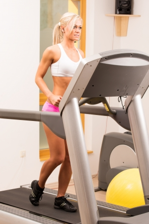 Young woman at the gym exercising  Run on on a machine  photo