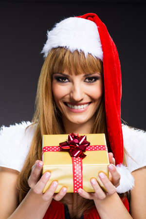 Portrait of young, sexy woman Santa with gift boxes photo