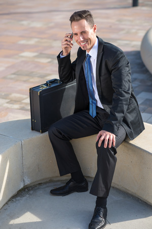 businessman waiting call: Successful young businessman calling the park