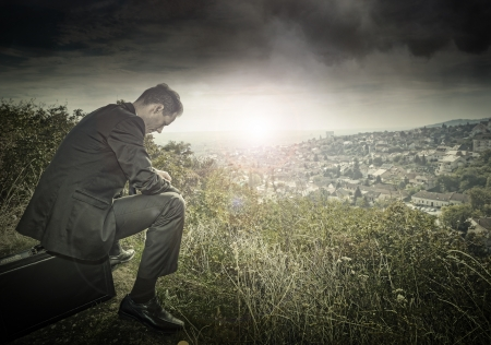 Sad, lonely businessman on the hillside photo