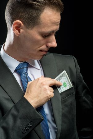 pulling money: Businessman pulling their money out of pocket