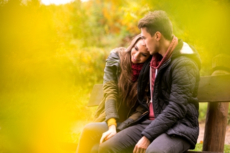 romantic sky: Loving couple in the autumn park sitting on a bench Stock Photo