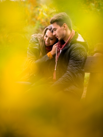 Loving couple in the autumn park sitting on a bench photo